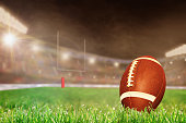 American football on field grass in brightly lit outdoor stadium with focus on foreground and shallow depth of field on background. Deliberate lens flare and copy space. Fictitious football stadium cr