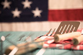 Outdoor or BBQ grilling utensils on outdoor rustic blue picnic table with USA flag in background.