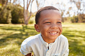 Outdoor Head And Shoulders Shot Of Young Boy In Park
