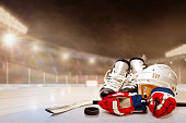 Ice hockey helmet, skates, stick and puck in brightly lit outdoor stadium with focus on foreground and shallow depth of field on background. Deliberate lens flare and copy space. Fictitious background