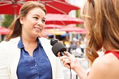 A woman being interviewed outdoors.