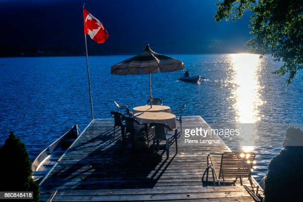Outdoor lifestyle by the lake in Canada, Non-recognizable person on the rowboat, patio furniture, canoe and Canadian flag at sunset. British Columbia Canada
