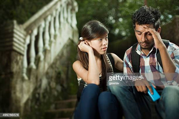 Outdoor on stairs girl consoling to sad boy in campus.