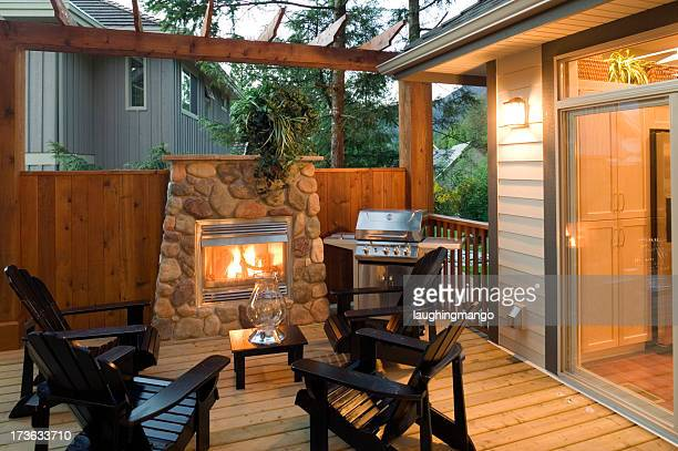 Outdoor patio with fireplace, chairs and barbeque grill