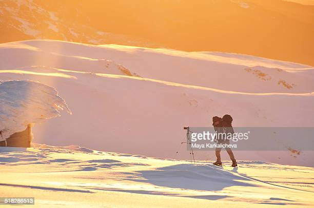 Outdoor photographer at sunset in Winter mountains