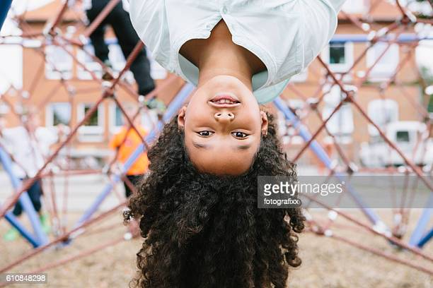 outdoor portrait: cute schoolgirl at climber, looking at camera