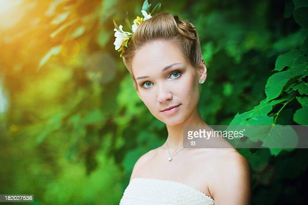 Outdoor portrait of a cute girl with flowers in hair