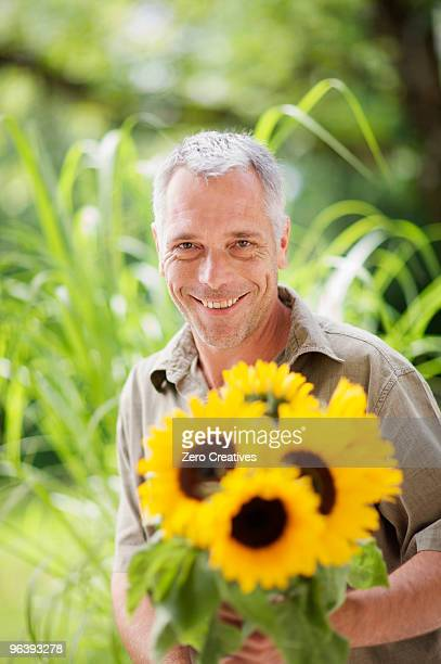 outdoor portrait of a man and sunflowers