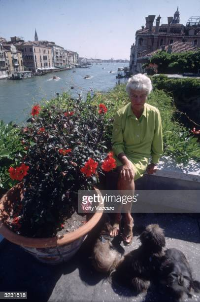 Outdoor portrait of American art collector Peggy Guggenheim sitting on her veranda overlooking the Grand Canal Venice Italy She sits beside a pot of...