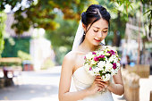 outdoor portrait of beautiful and happy young asian bride wearing bridal veil.