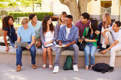Outdoor Portrait Of High School Students On Campus Sitting Outside Holding Laptop, Digital Tablet and Text Book. Talking And Smiling To Each Other