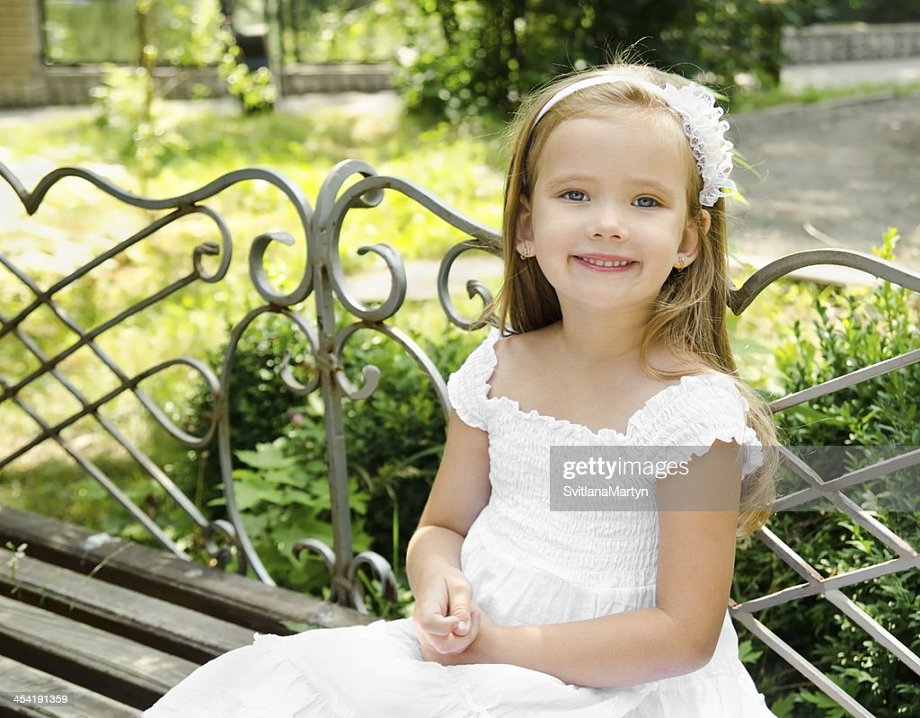 Outdoor portrait of little girl sitting on a bench : Stock Photo