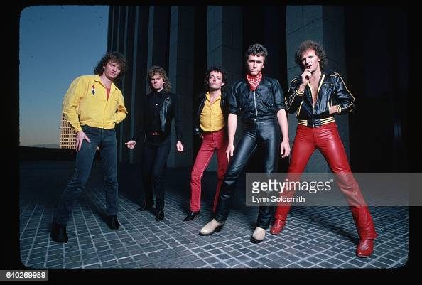Outdoor portrait of Loverboy Band members are shown fulllength posing outside a city building at dusk Photograph 1981