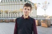 Outdoor portrait of smiling teenager boy 14, 15 years old. City background, golden hour