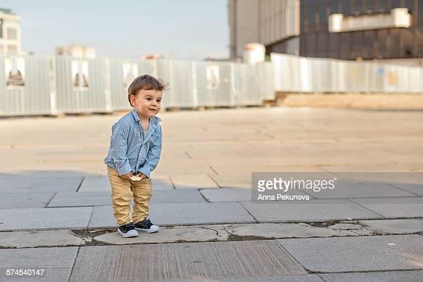 Outdoor portrait of toddler boy bending forward