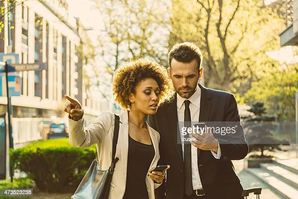 Outdoor portrait of two business people with smart phones