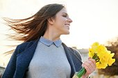 Outdoor portrait of young beautiful girl with bouquet of yellow spring flowers.