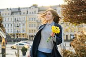 Outdoor portrait of young beautiful girl with bouquet of yellow spring flowers, background city street, architecture.