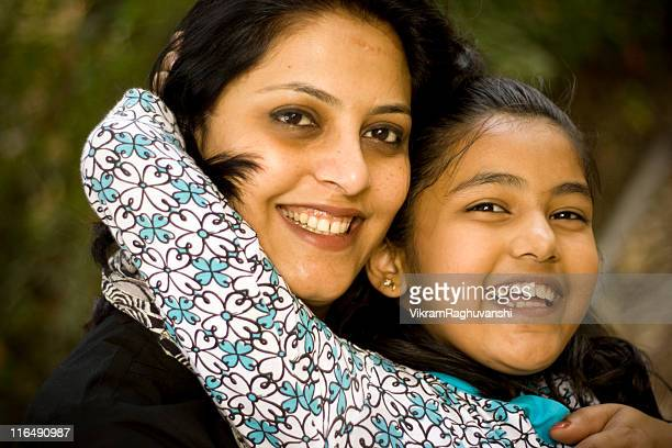 Outdoor portrait of young cheerful attractive Indian mother and daughter