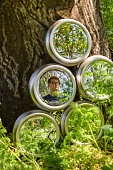 A portrait of a young man reflected in a mirror that is propped up against a tree and surrounded by vibrant nature.