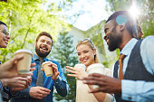 Joyful business team with coffee interacting in park