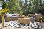 Villa patio with stylish rattan furniture and pattern carpet