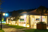 outdoor restaurant under huge tent at night on view from grassland