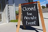 "Outside a shop, a black chalkboard-style hanging sign reads ""closed for private event""."