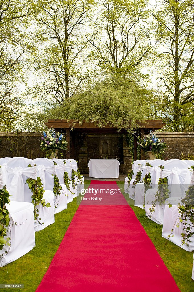 Outdoor wedding location with a red carpet aisle