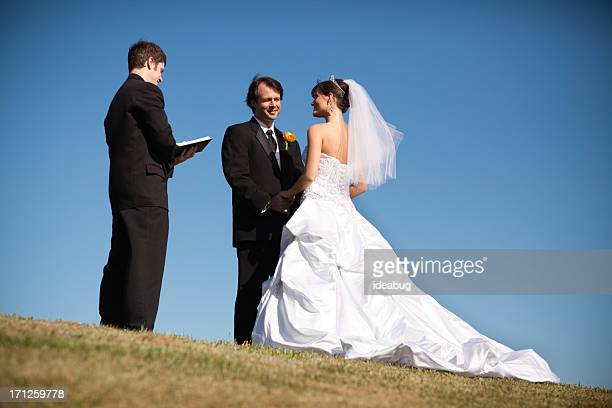 Outdoor Wedding of Happy Bride and Groom, With Minister