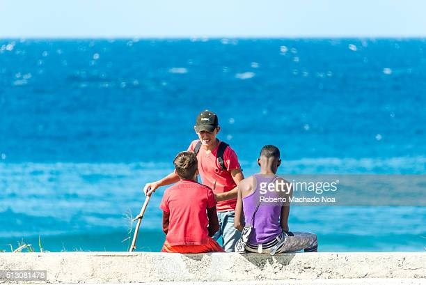 Outdoor youth Three teenager boys siting down by the sea in East Havana