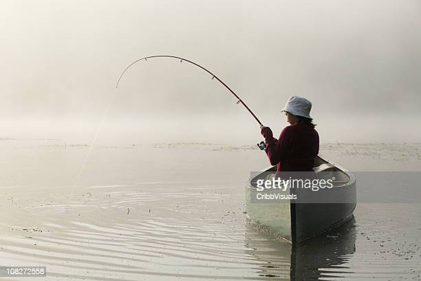 Outdoors girl catching fish from canoe on misty morning lake