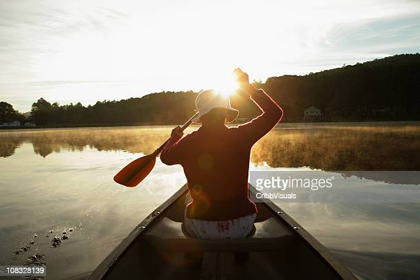 Outdoors girl paddling canoe on lake in bright misty sunrise