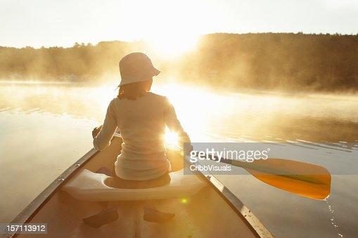 Outdoors girl paddling canoe on lake in bright misty sunrise