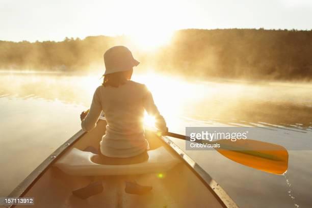 屋外パドルカヌー女の子に明るい霧の湖の日の出