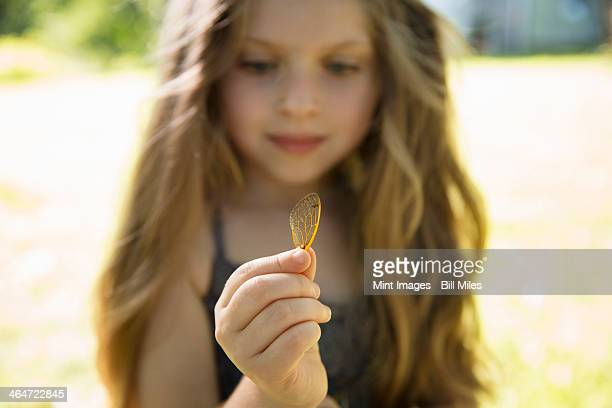 Outdoors in summer. A young girl with long blonde, holding a delicate lacy patterned discarded butterfly wing.