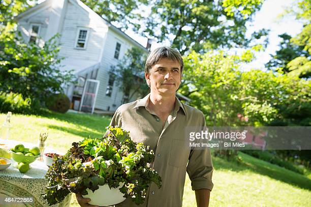Outdoors in summer. On the farm. A man in a farmhouse garden, carrying a large bowl of freshly picked organic lettuce and salad leaves.