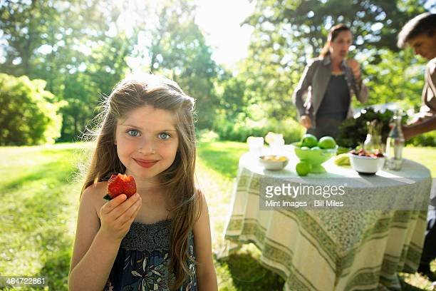 Outdoors in summer. On the farm. Children and adults together. A young girl holding a large fresh organically produced strawberry fruit. Two adults beside a round table.