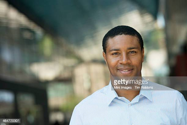 Outdoors in the city. In a public space. Business people on the move. A man in an open necked shirt smiling.