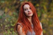 Outdoors portrait of beautiful young woman with red hair colorful autumn