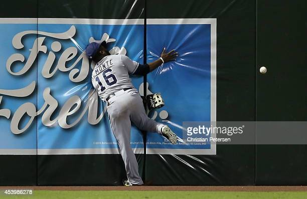 Outfielder Abraham Almonte of the San Diego Padres crashes into the wall as he attempts to catch a double hit by Miguel Montero of the Arizona...