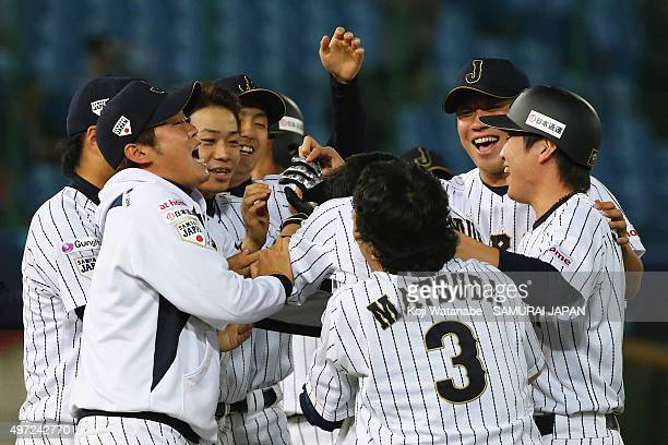 Outfielder Akira Nakamura of Japan is congratulated by his team mates after the walkoff victory in the WBSC Premier 12 match between Venezuela and...