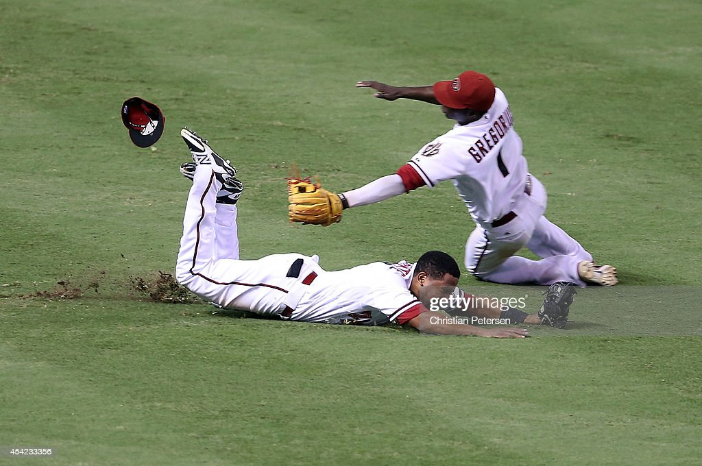 Outfielder Alfredo Marte #17 (L) of the Arizona Diamondbacks makes a diving catch as <a gi-track='captionPersonalityLinkClicked' href=/galleries/search?phrase=Didi+Gregorius&family=editorial&specificpeople=8945889 ng-click='$event.stopPropagation()'>Didi Gregorius</a> #1 slides in during the ninth inning of the MLB game against the Los Angeles Dodgers at Chase Field on August 26, 2014 in Phoenix, Arizona. The Dodgers defeated the Diamondbacks 9-5.