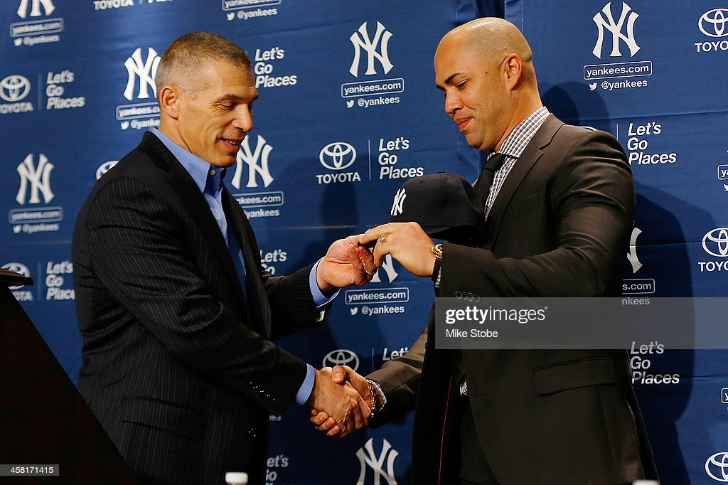 Outfielder <a gi-track='captionPersonalityLinkClicked' href=/galleries/search?phrase=Carlos+Beltran&family=editorial&specificpeople=167108 ng-click='$event.stopPropagation()'>Carlos Beltran</a> is presented with his hat by manager <a gi-track='captionPersonalityLinkClicked' href=/galleries/search?phrase=Joe+Girardi&family=editorial&specificpeople=208659 ng-click='$event.stopPropagation()'>Joe Girardi</a> during Beltran's introductory press conference at Yankee Stadium on December 20, 2013 in the Bronx borough of New York City.