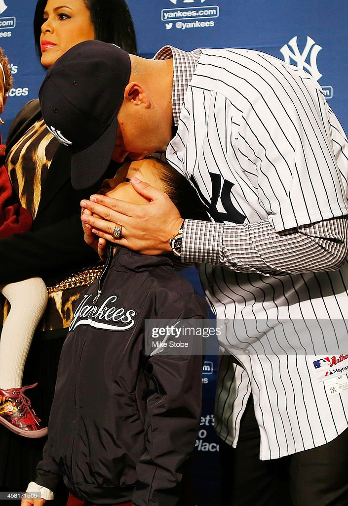 Outfielder Carlos Beltran kisses his daughter Ivana during his introductory press conference at Yankee Stadium on December 20, 2013 in the Bronx borough of New York City.
