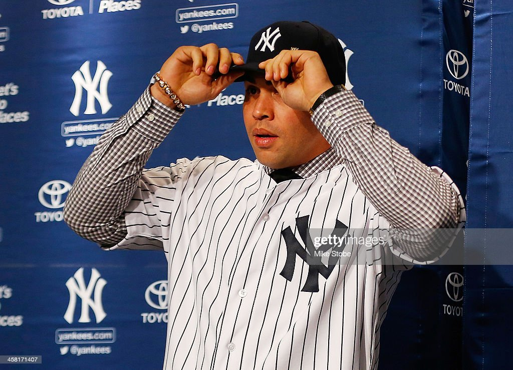 Outfielder <a gi-track='captionPersonalityLinkClicked' href=/galleries/search?phrase=Carlos+Beltran&family=editorial&specificpeople=167108 ng-click='$event.stopPropagation()'>Carlos Beltran</a> puts on his hat during his introductory press conference at Yankee Stadium on December 20, 2013 in the Bronx borough of New York City.