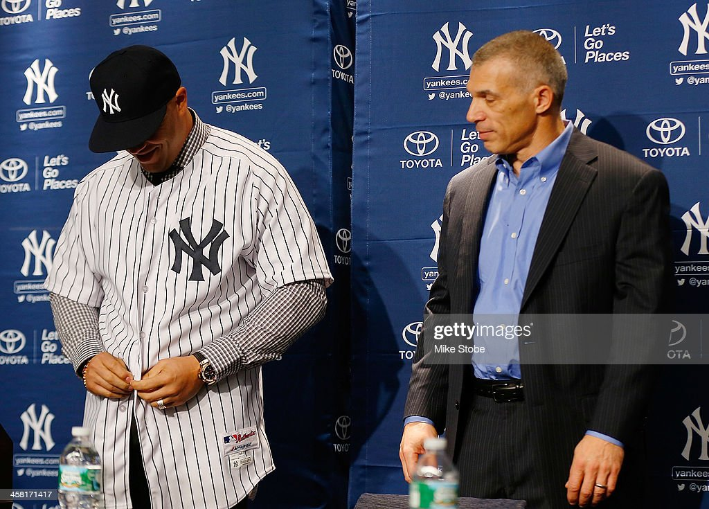Outfielder <a gi-track='captionPersonalityLinkClicked' href=/galleries/search?phrase=Carlos+Beltran&family=editorial&specificpeople=167108 ng-click='$event.stopPropagation()'>Carlos Beltran</a> puts on his jersey as Manager <a gi-track='captionPersonalityLinkClicked' href=/galleries/search?phrase=Joe+Girardi&family=editorial&specificpeople=208659 ng-click='$event.stopPropagation()'>Joe Girardi</a> look on during Beltran's introductory press conference at Yankee Stadium on December 20, 2013 in the Bronx borough of New York City.