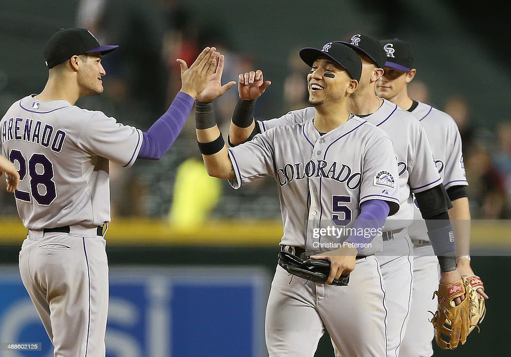 Outfielder Carlos Gonzalez #5 of the Colorado Rockies high-fives Nolan Arenado #28 after defeating the Arizona Diamondbacks in the MLB game at Chase Field on April 29, 2014 in Phoenix, Arizona. The Rockies defeated the Diamondbacks 5-4.