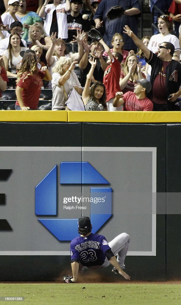 Outfielder Charlie Culberson #23 of the Colorado Rockies slips and falls as he watches a ground rule double by Miguel Montero #26 of the Arizona Diamondbacks bounce over the fence during the sixth inning of a MLB game at Chase Field on September 14, 2013 in Phoenix, Arizona.