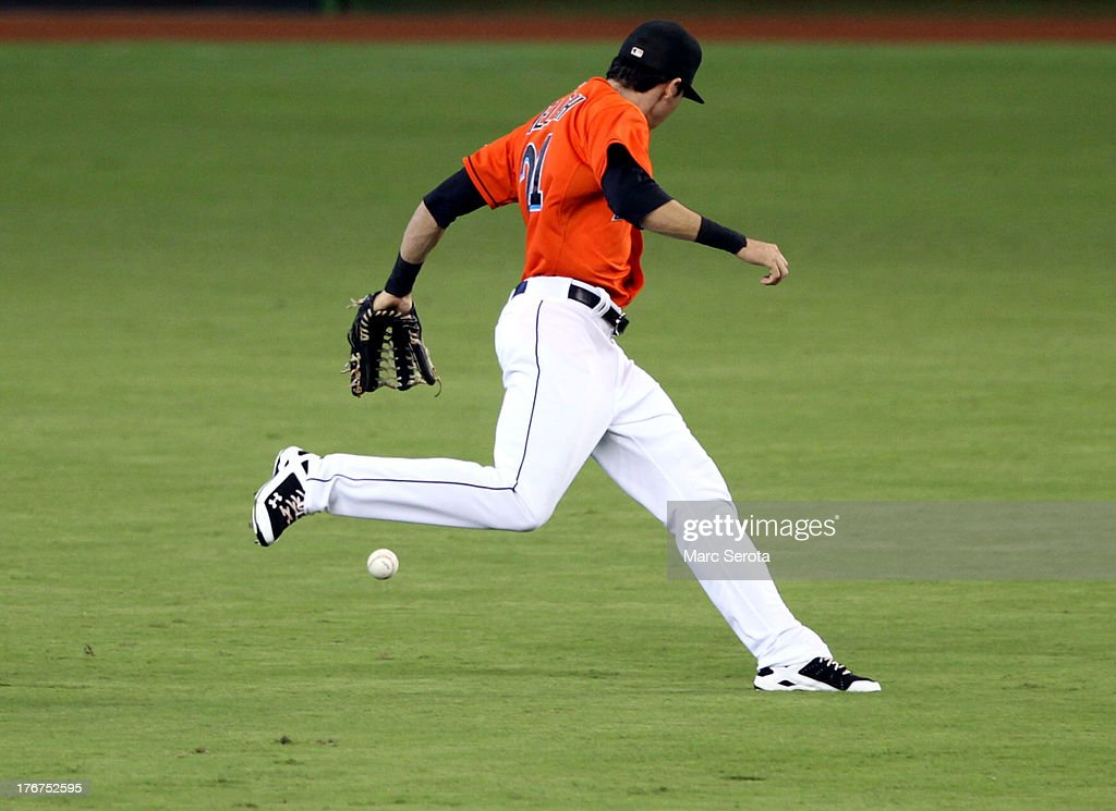 Outfielder Christian Yelich #21 of the Miami Marlins drops the ball against the San Francisco Giants at Marlins Park on August 18, 2013 in Miami, Florida.